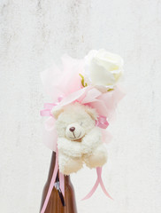 white rose with bear doll in brown bottle