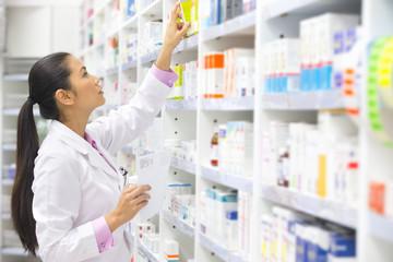 Pharmacist, holding prescription, looking for medication on pharmacy shelf