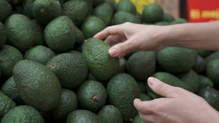 Woman Shopping For Avocados Handheld