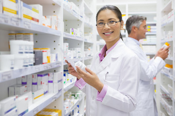 Pharmacist, holding medication pot and prescription, in pharmacy