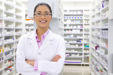 Pharmacist, with arms crossed, in pharmacy