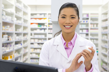 Pharmacist holding medication pot, from behind pharmacy counter
