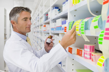 Pharmacist holding medication pot looking at labels on pharmacy shelf
