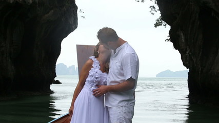 handsome groom in white suit kiss his blonde bride in wedding dr