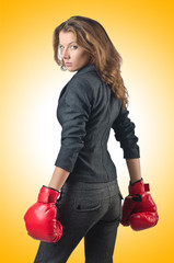 Young businesswoman in boxing concept