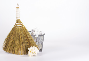 isolated besom and wastebasket full of waste paper