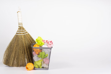 isolated besom and wastebasket full of color waste paper