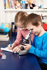Girl and boy uses a microscope and writes results