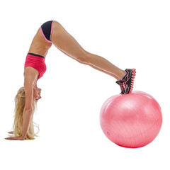 Energetic girl doing handstand on fitness ball