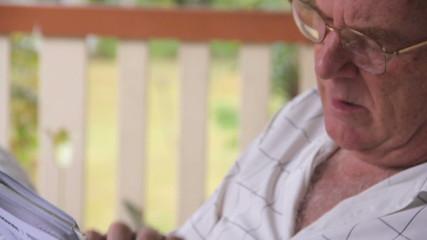 Man sitting and relaxing on his verandah playing sudoku.