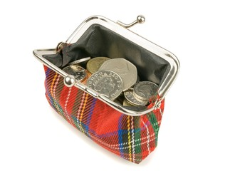 An open purse full of British money coins on a white background