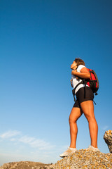 woman hiker stands on  mountain rock