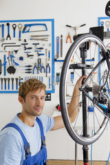 Cycle technician looking at camera in workshop