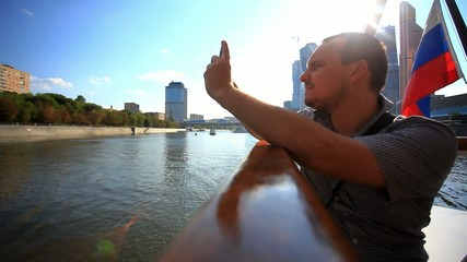 man taking picture with smartphone on a cruise ship and waving