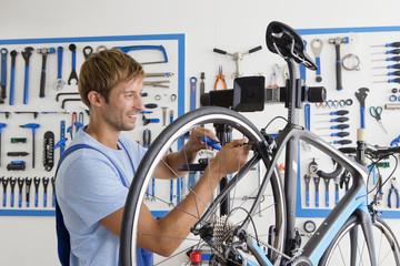 Cycle technician repairing bicycle