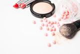 Fototapety the bronzing pearls, lipstick and makeup brush.