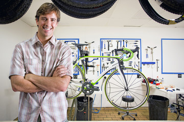 Store owner or customer in bicycle shop smiling at camera