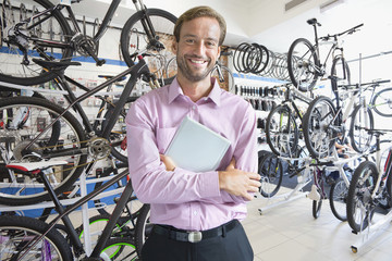 Store owner in bicycle shop smiling at camera