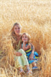 Mother with  daughter in the field of ripe wheat