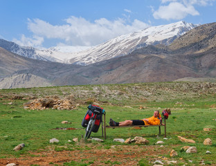 Young tourist cyclist lying resting in high mountains