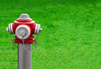 Modern red hydrant on a green grass background