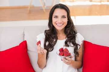 Pretty brunette eating strawberries on couch