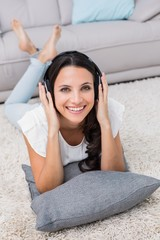 Pretty brunette lying on the rug listening to music