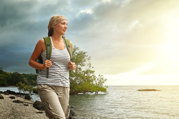 Tourist girl enjoying view of beautiful sunset and sea