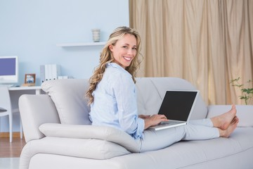 Smiling blonde on couch using laptop