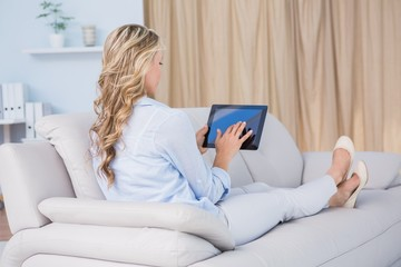 Blonde woman sitting on couch using tablet