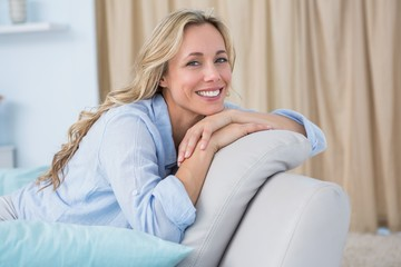 Cheerful pretty blonde sitting on couch