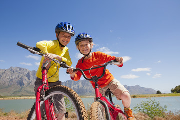 Portrait of children on mountain bikes by lake