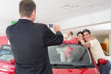 Businessman taking picture of the couple in their new car