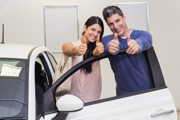 Smiling couple standing while giving thumbs up