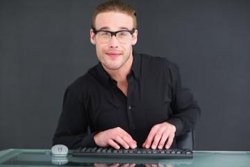 Smiling businessman typing on keyboard