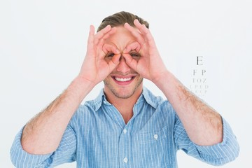 Smiling doctor forming eyeglasses with his hands