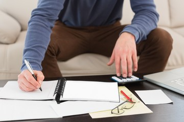 Man using calculator and taking notes