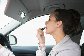 Woman using mirror to put on lipstick while driving