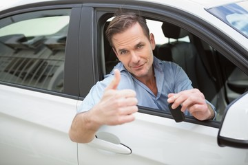Smiling man giving thumbs up and holding key