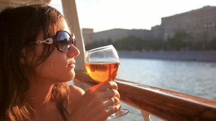 thoughtful woman looking on beautiful sunset with glass of red