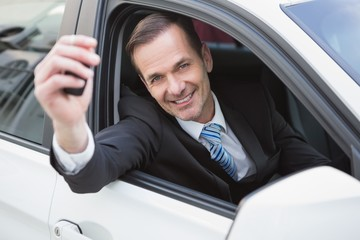 Businessman smiling and showing key