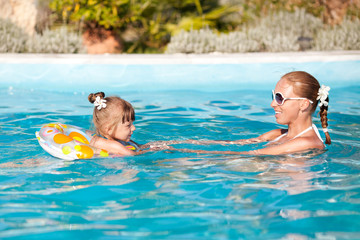Happy Little Girl And Mother In Pool