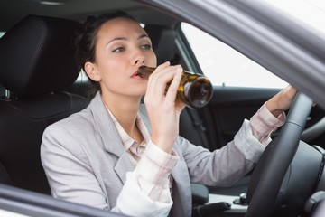 Woman drinking beer while driving