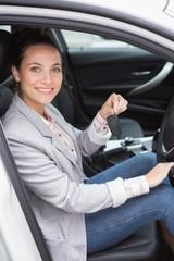 Woman smiling at camera showing key