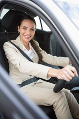 Pretty businesswoman smiling and driving