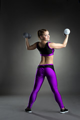 Slim athletic gymnast exercising with dumbbells