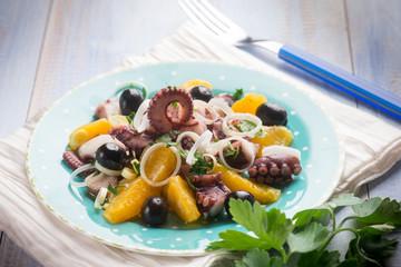 octopus salad with sliced orange, selective focus