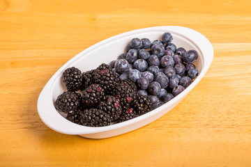 Black and Blue Berries in White Bowl on Wood Table