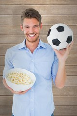 Composite image of handsome young man holding ball and popcorn