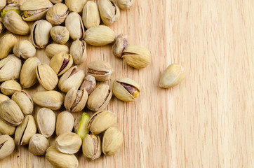 roasted and salted pistachios on wooden background